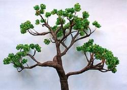 7. Сборка дерева бонсай из бисера.  Возьмите центральную ветку и, прикладывая к ней ветки, выберите нужную.