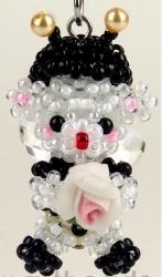 Маленький объемный медведь в шапочке с рожками и розочкой в лапках.  Изделие сплетено из бисера.